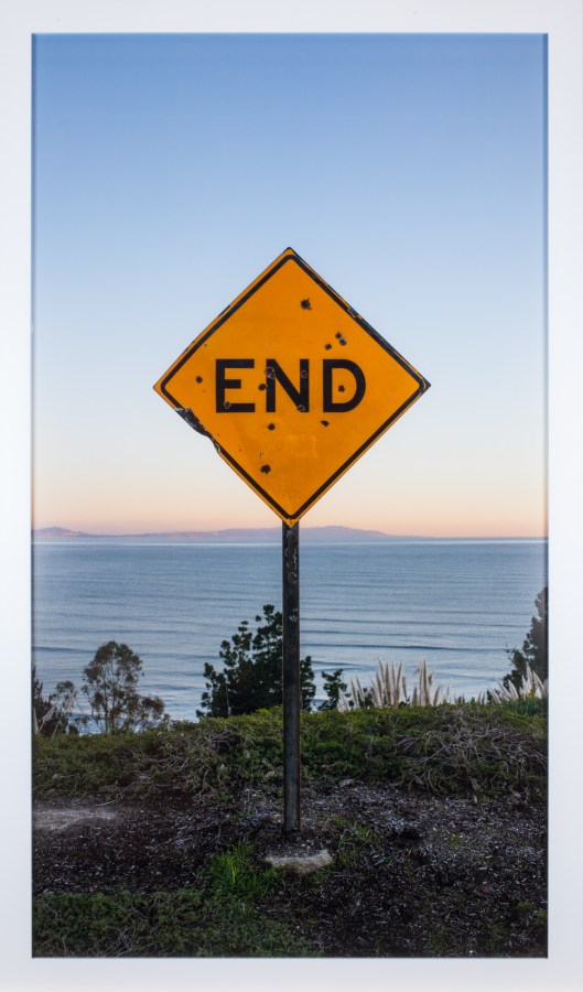"""A framed photograph of a road sign reading """"END,"""" at the edge of a grassy cliff overlooking the water"""