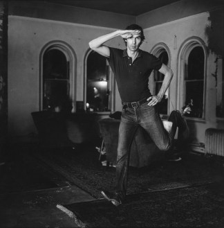 Black-and-white photograph of a white man jumping in a furnished room