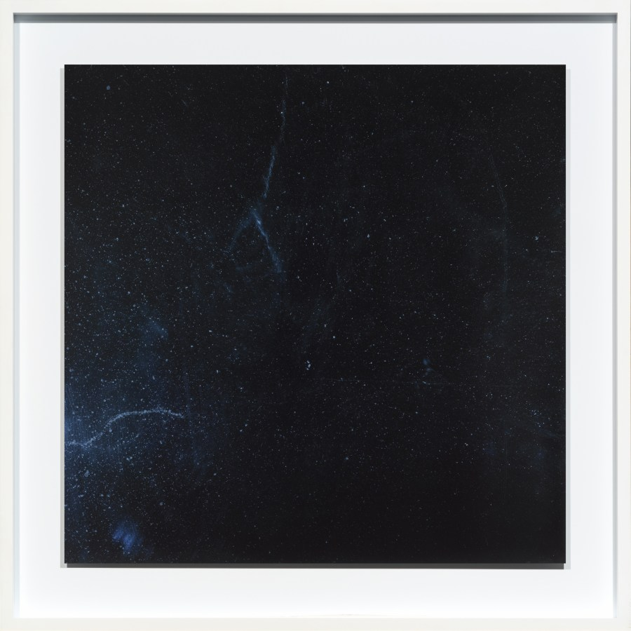 Color photograph of an empty dark blue surface with spots and streaks of dust