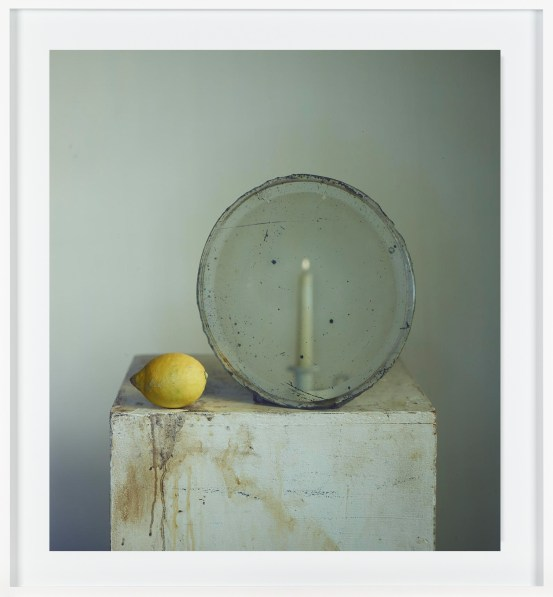 Color photograph of mirror, candle, and lemon on plinth