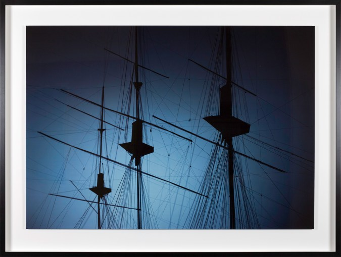 Color photograph of three masts of a ship against a blue sky
