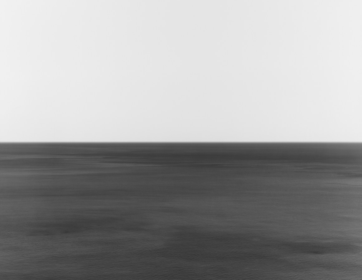 A black and white photograph of a seascape, with the horizon exactly in the middle of the frame. The water is rippled with some darker waves.