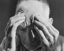 Black-and-white photograph of an old man pushing his fingers into his temples.