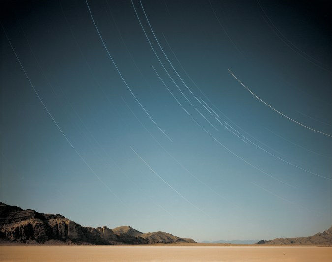 Color photograph of a beach with a mountain range on the horizon under a sky filled with long-exposure curved star-trails