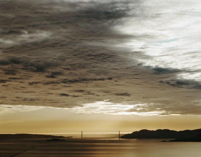 Color photograph of the distant Golden Gate Bridge at sunset under a cloudy sky