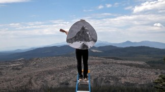 Video still of a person on a step stool holding a guitar in a mountainous landscape with a circular illustration of a mountain overlaid on top of him