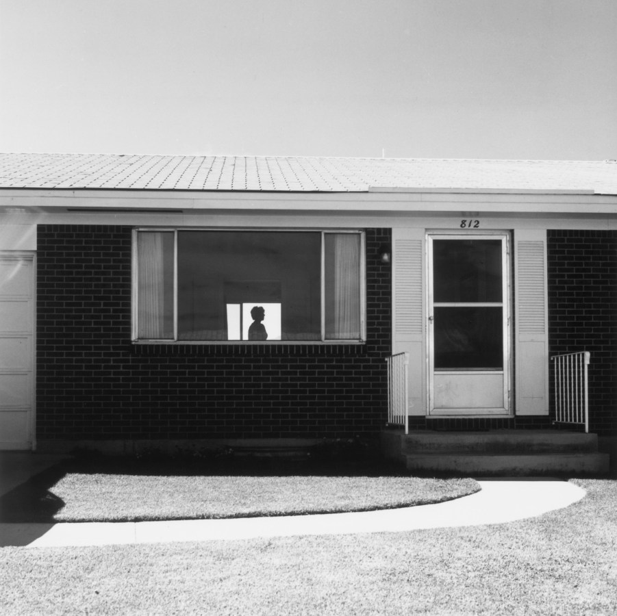Black-and-white horizontal photograph of a suburban home, with a figure silhouetted in the window.