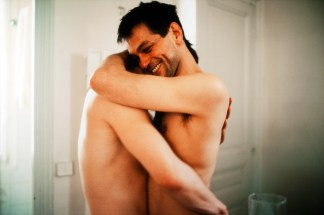 Color photograph of two shirtless white men hugging.