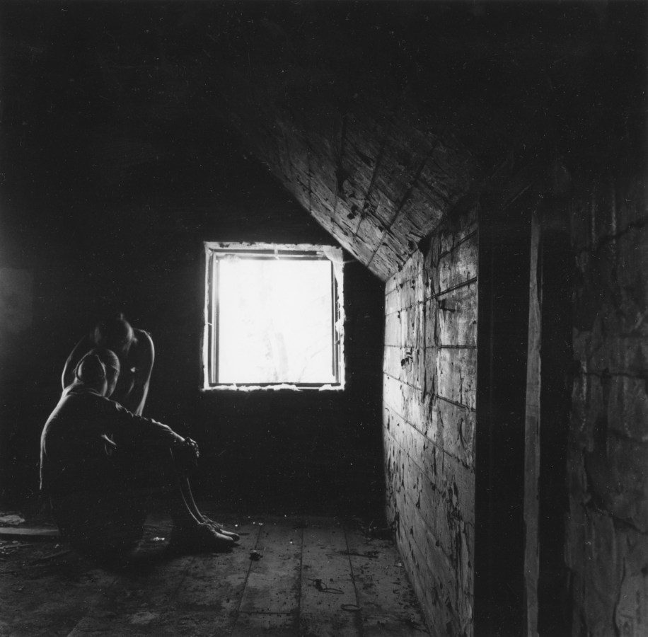 Black-and-white photograph of two figures seated in an attic room next to a square window