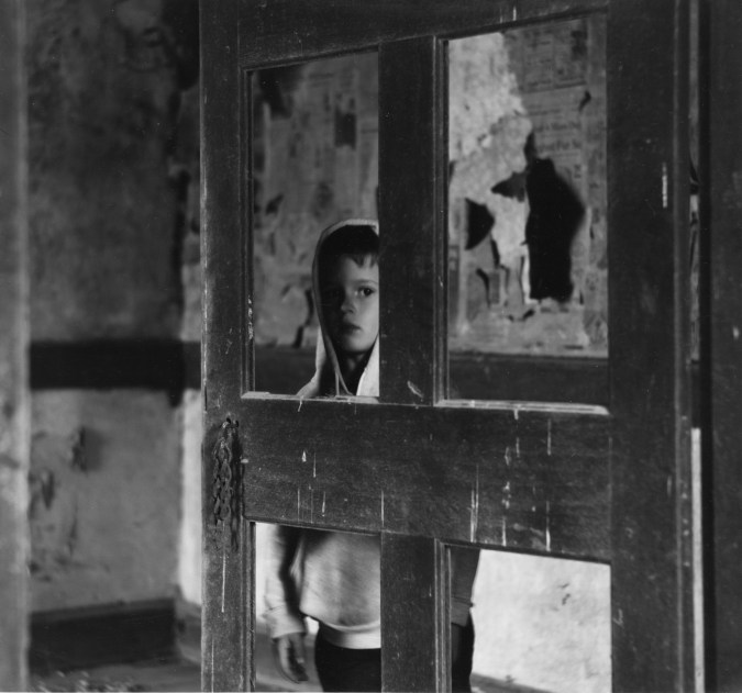 Black-and-white photograph of a young boy in a hooded sweatshirt looking through a door with missing panels from a decrepit room