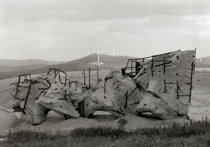 Black-and-white horizontal photograph of a concrete-and-metal armature in a hilly landscape.