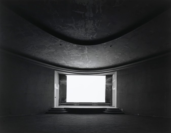 Black-and-white photograph of an empty theater with a glowing blank white screen