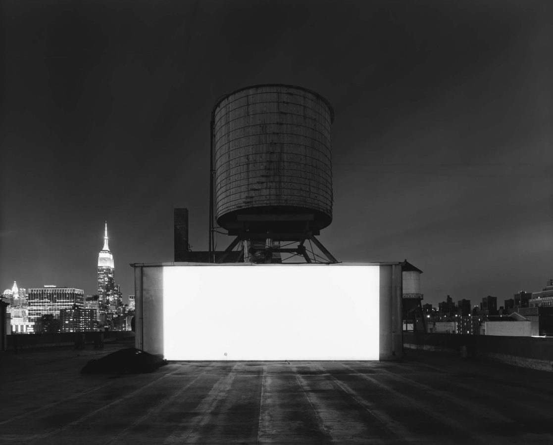 Black-and-white photograph of a glowing blank white screen against a water tower and city night skyline
