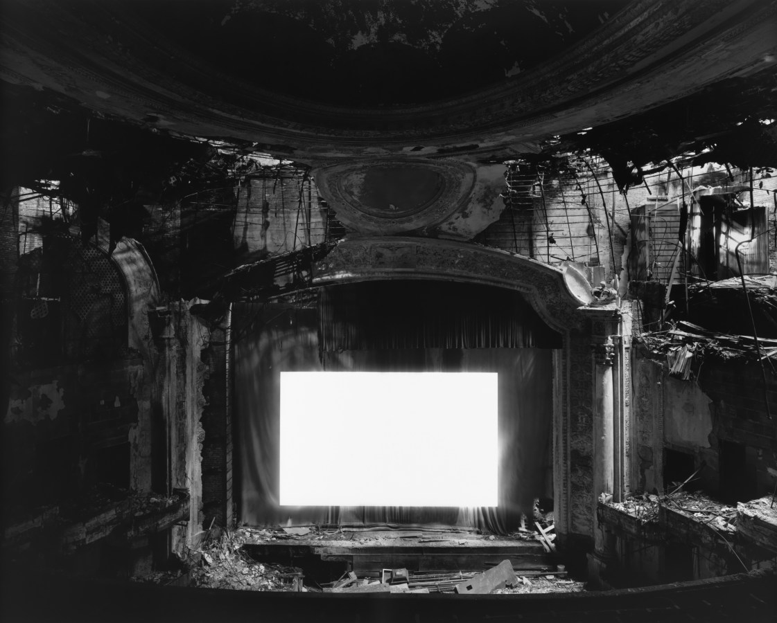 Black-and-white photograph of an derelict abandoned theater with a glowing blank white screen