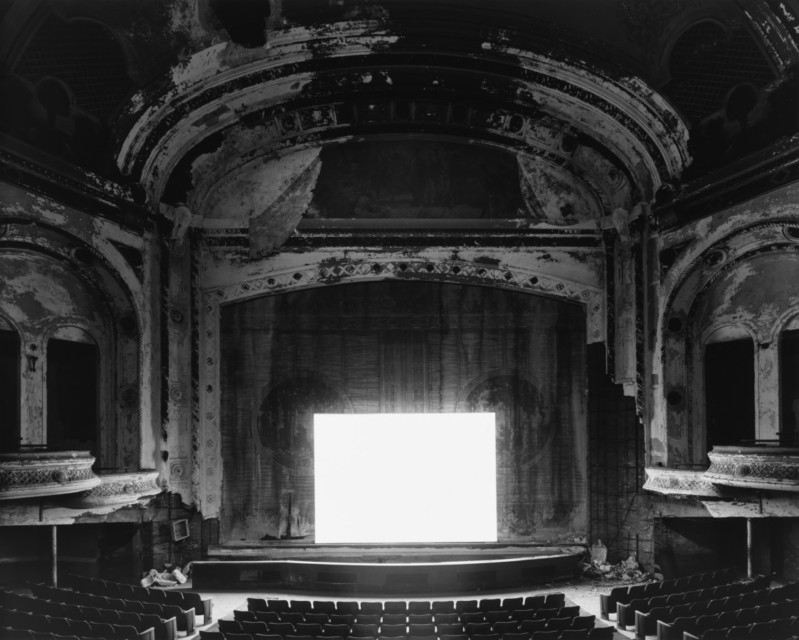 Black-and-white photograph of an empty abandoned theater with a glowing blank white screen