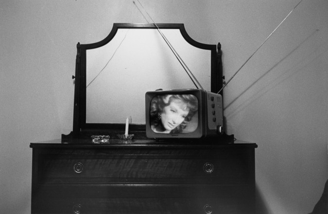 Black-and-white photograph of a television with a woman's face onscreen on top of a bureau