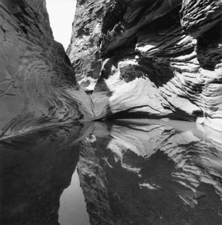 Black-and-white photograph of rock formations and their reflection in a body of water