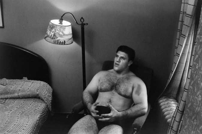 Black-and-white photograph of a shirtless man sitting in a bed room next to a lamp