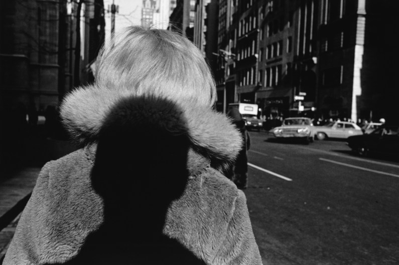 Black-and-white photograph of the shadow of a persons head on the back of a woman