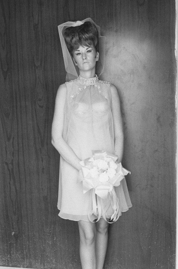 A black and white photograph of a woman wearing a see through bridesmaid dress and holding a bouquet in front of a wood paneled wall