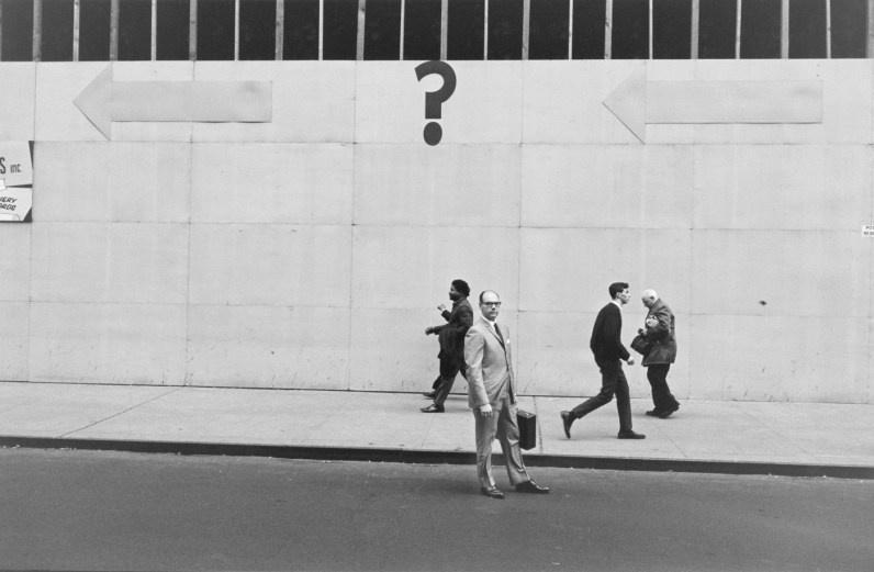 Black-and-white photograph of a man in a suit standing in the street in front of a. building with a question mark painted on it