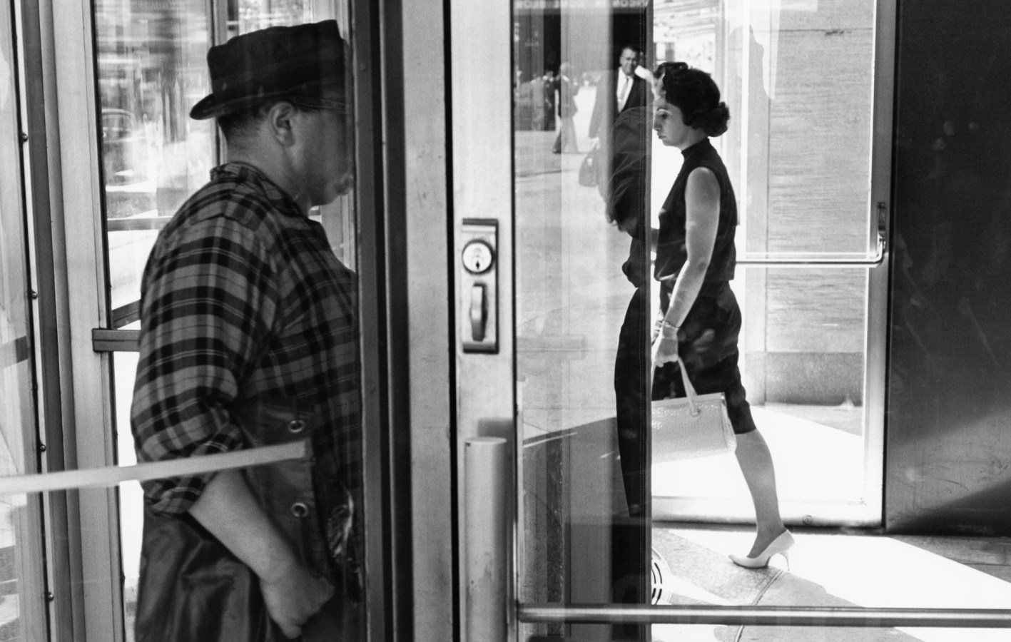Black-and-white photograph of a man and woman entering and exiting a building with their faces obscured by doors