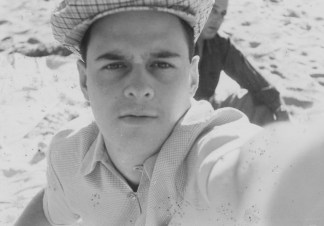 Black-and-white selfie photograph of a white man in a button-up shirt and cap.