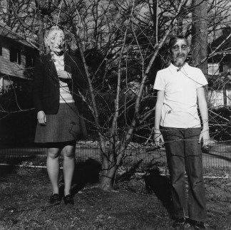 Black-and-white photograph of two people in Halloween masks standing on either side of a leafless tree.
