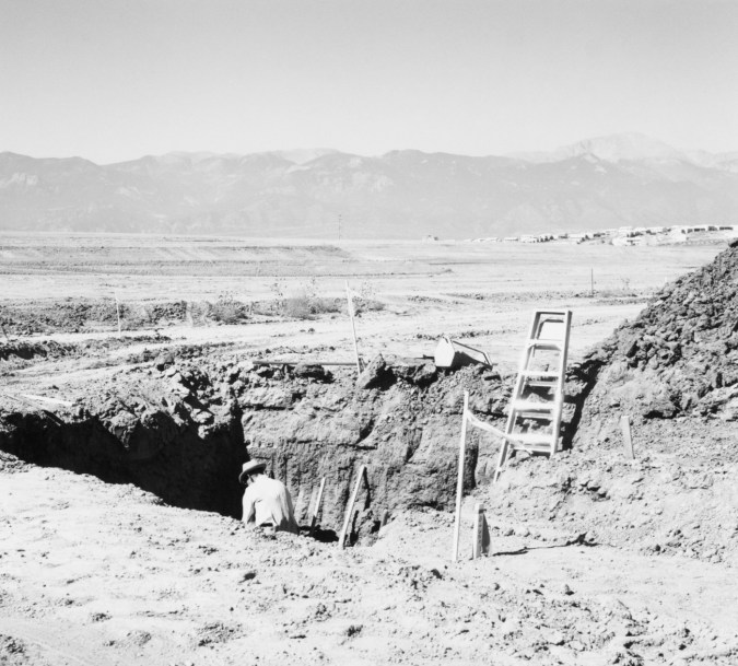 A black and white photograph of a lone person digging with mountains in the background.