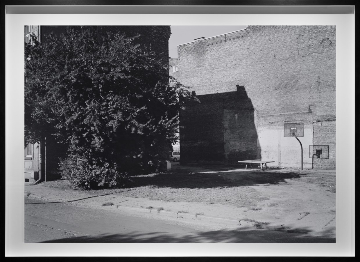 Black-and-white photograph of an empty basketball court against a the side of a bare brick building
