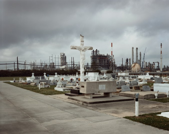 Color photograph of a white crucifix with attached figure of Christ rising above smaller graves with power plant buildings in the background