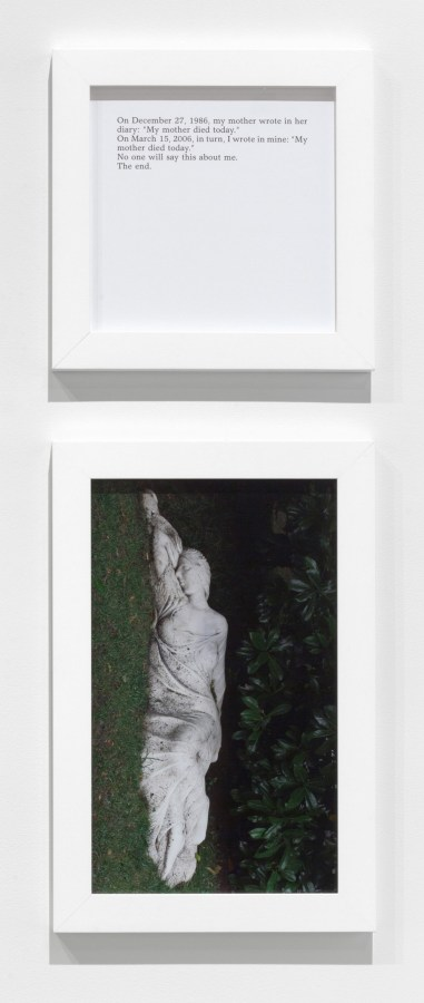 A square framed text panel hanging over a framed photograph of a sculpture of a woman lying on the ground