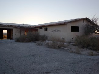 """Color photograph of an abandoned home with grafitti reading """"Desolation"""""""