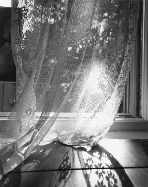 Black-and-white photographs of light coming through a lace curtain