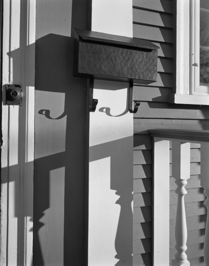 Black-and-white photograph of a metal mailbox on the wall of a clap-board sided house