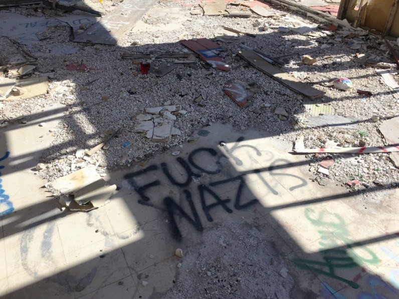 Color photograph of black spray-painted writing reading FUCK NAZIS on a tile floor covered in debris