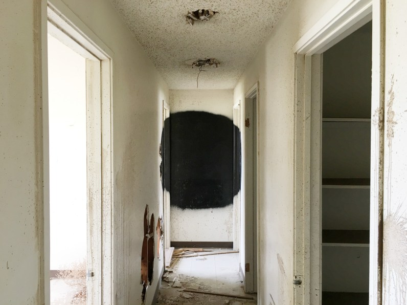 Color photograph of a black spray-painted circle at the end of a white hallway of an abandoned building