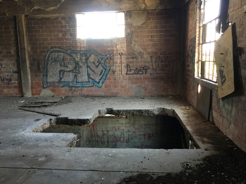 Color photograph of the spray-painted interior of an abandoned brick building with a hole in the floor leading to the lower level