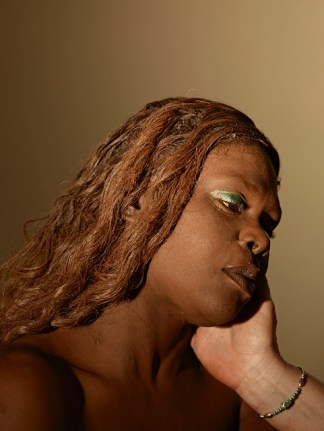 Color photograph of an African American woman, with a white hand touching her face.