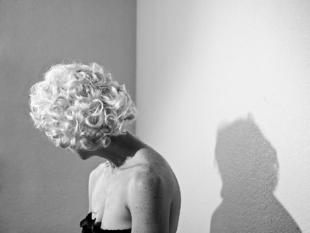 Black-and-white photograph of a woman in a blonde wig, turned away from the camera