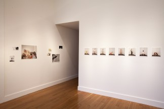 Installation photograph of a gallery space with small unframed prints on the walls