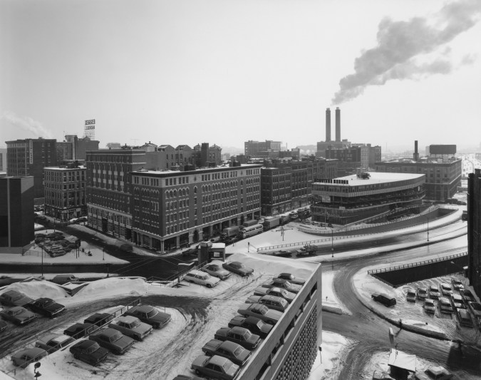 Black-and-white photograph of a city intersection in winter with a rooftop garage and smokestacks