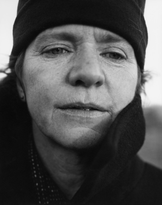 Black-and-white photographic portrait of a woman wearing a black hat