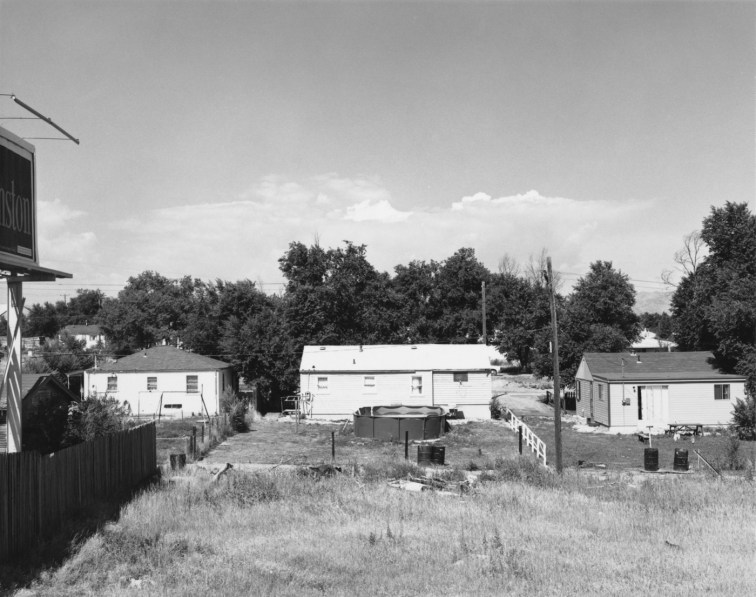 A black and white photograph of the backyards of suburban houses with an above ground swimming pool in the center and a bill board on the left side.