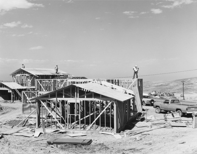 A black and white photograph of three construction workers on the roofs of unfinished houses.