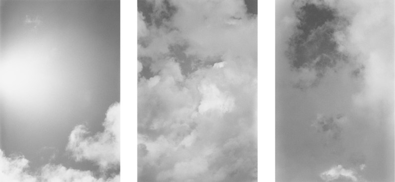 Three black-and-white vertical photos of clouds and a brightly lit sky