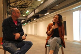 Video still of two people seated in a gallery during a panel discussion