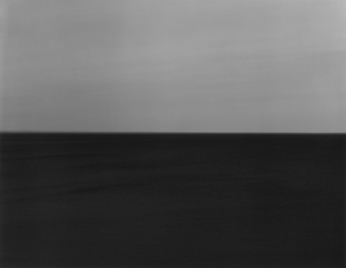 Black-and-white photograph of a seascape with a dark gray sky and very dark water