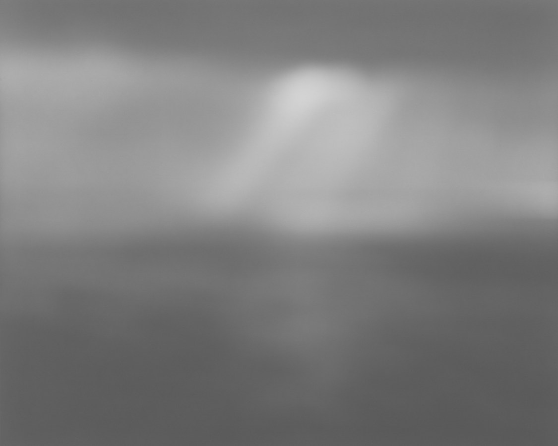 Black-and-white photograph of a very foggy seascape, with a ray of light in the center of the sky