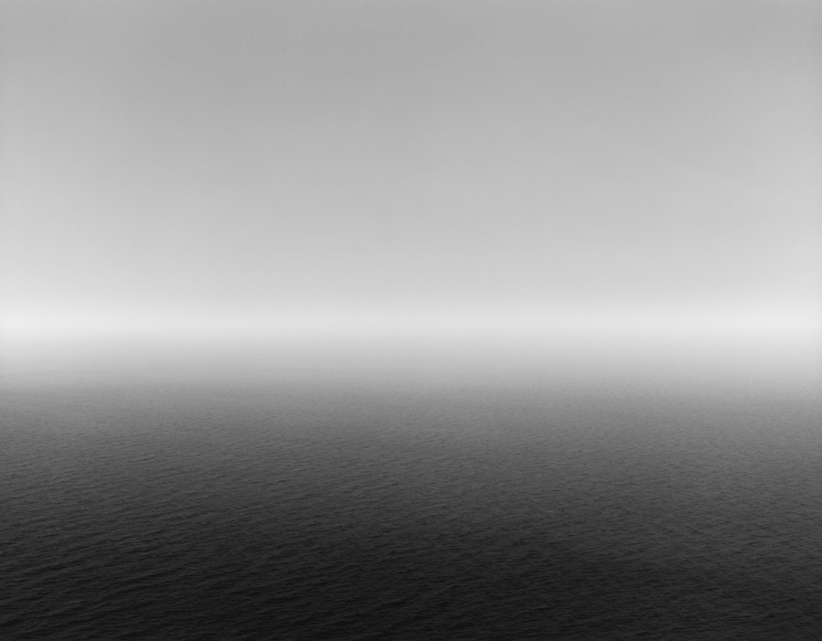 Black-and-white photograph of a seascape, with very bright light on the horizon and a dark foreground